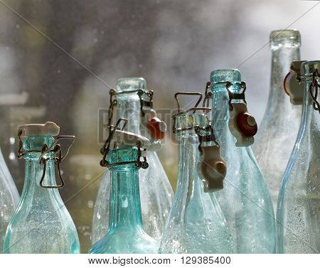 Group of back lit blue and transparent old fashioned empty glass bottles in a window