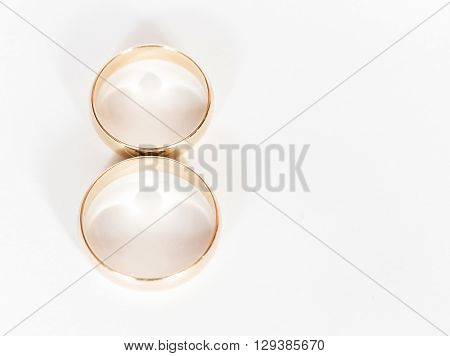 Two gold wedding rings close up on a white background