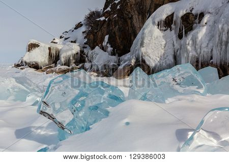 Transparent icicles in the snow on a background of icy rocks. Beautiful winter landscape in the Lake Baikal.