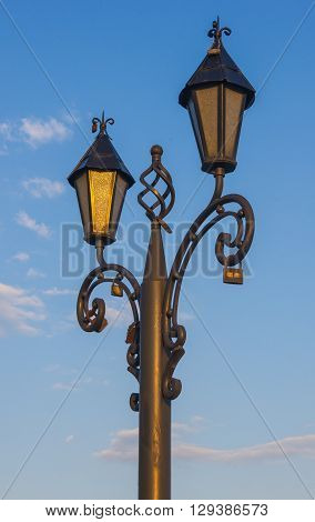 city skyline - classic lamp post with locks of lovers at sunset