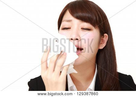 portrait of businesswoman with an allergy sneezing into tissue on white background