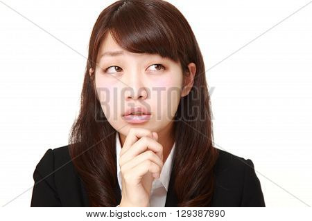 portrait of young Japanese businesswoman worries about something on white background