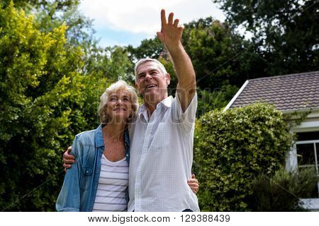 Happy senior man pointing while standing with wife in back yard