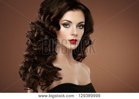 Brunette woman with curly hairstyle. Beautiful girl with long wavy hair. Perfect makeup. Fashion photo