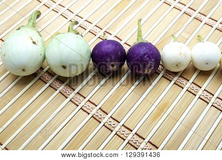 Green brinal,  white eggplants and violet/purple eggplants on brown bamboo mat.