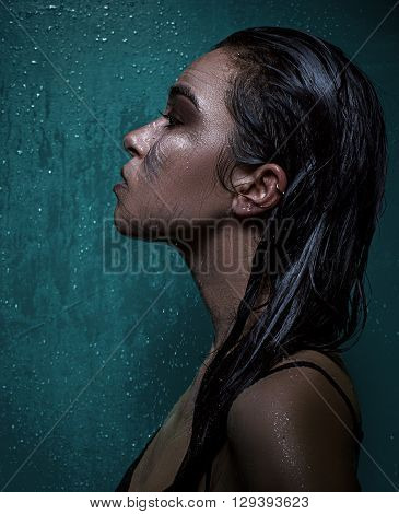 wet Beautiful brunett girl under shower over blue