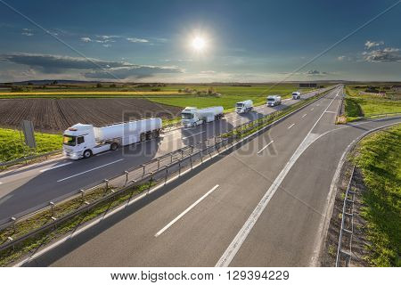 Many white gasoline tanker trucks in line driving towards the sun. Fast gasoline delivery on the freeway at beautiful idyllic day. Freight scene on the motorway near Belgrade Serbia.