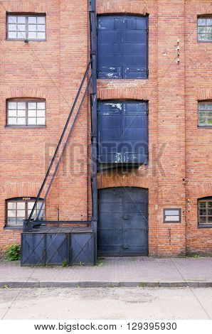 Old style red brick building and three metal doors and windows on it and old hoist