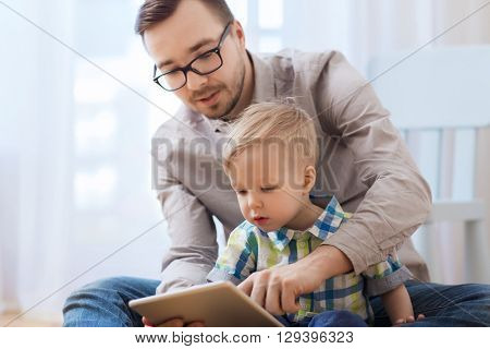 family, childhood, fatherhood, technology and people concept - happy father and son with tablet pc computer playing at home