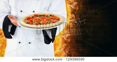 Close up on a chef presenting a pizza against dark wall