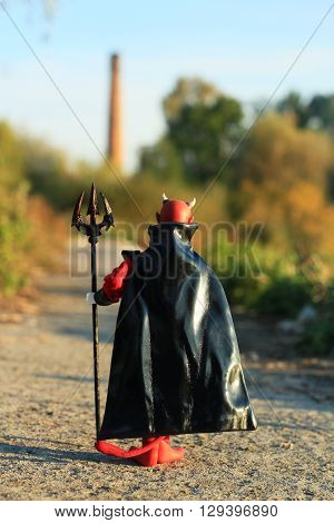 Doll of Devil with forks on the road