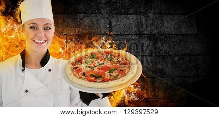 Portrait of a woman chef holding a pizza against green wall