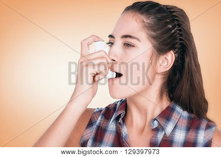 Woman having asthma using the asthma inhaler against orange vignette