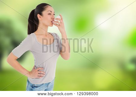 Asthmatic pretty brunette using inhaler against glowing sky above field