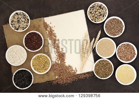 Healthy grain food in round porcelain bowls and loose with natural hemp paper notebook and wheat sheaths over lokta paper background.