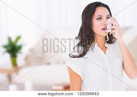 Asthmatic brunette using her inhaler against light bulb flower on dark wall