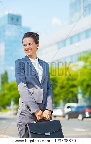 Business Woman With Briefcase In Office District Looking Aside