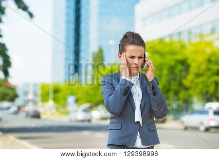 Stressed Business Woman In Office District Talking Smartphone