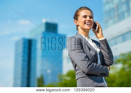 Smiling Business Woman In Office District Talking Cellphone