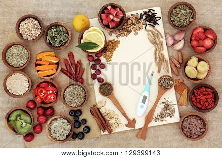 Health food selection for cold remedy to boost immune system, high in antioxidants, anthocyanins, minerals and vitamins with thermometer on natural hemp notebook.