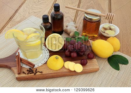 Cold remedies with cough medicine, vitamin c tablets, honey, grapes, spices and hot lemon drink on maple board over bamboo and oak background.