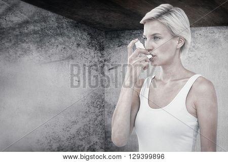 Blonde woman taking her inhaler against image of room corner