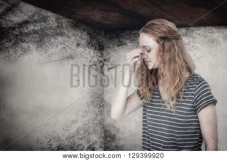 Blonde woman with headache pinching her nose against image of room corner