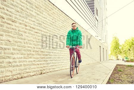 people, style, leisure and lifestyle - young hipster man riding fixed gear bike on city street over building brick wall background