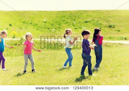 summer, childhood, leisure and people concept - group of little kind catching soap bubbles outdoors