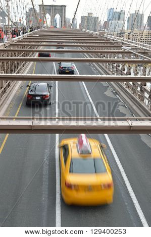 Yellow taxi on the Brooklyn Bridge NYC.