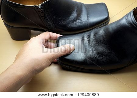 Thumb Pressing Down on head of black leather shoe on wooden floor. Focus on finger.