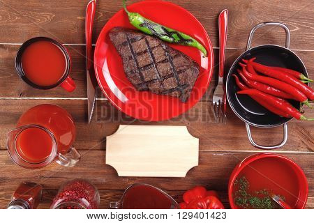 red theme lunch : fresh grilled bbq roast beef steak red plate tomato soup ketchup sauce paprika jug glass ground pepper american peppercorn modern cutlery served on wooden table with empty nameplate