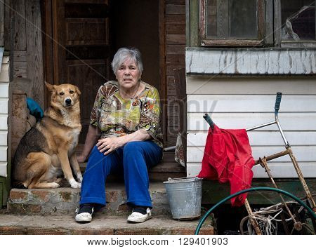 Elderly woman with a dog on the porch of the old farmhouse. Concept - old age, poverty, loneliness in old age