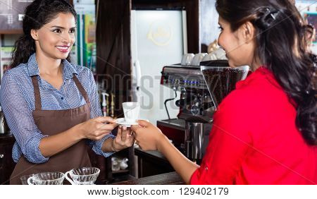 Bartender serving customer in Indian cafe