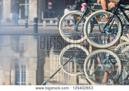 People Riding Bicycles In The Mirror Fountain