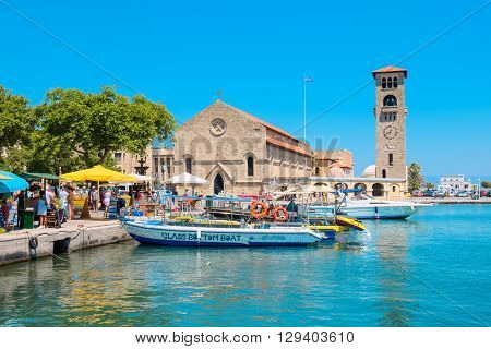 RHODES GREECE - JULY 4 2015: Tourists walking in Mandraki harbour near Church of the Evangelismos (Annunciation)