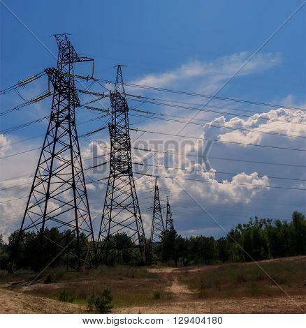 electricity transmission pylon silhouette against blue sky.