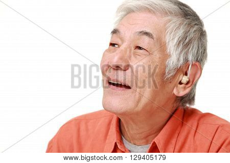 portrait of senior Japanese man with hearing aid on white background