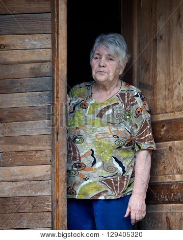 Portrait of an elderly woman. The old woman stands in the doorway of the village, wooden house. The old woman is waiting. Touching, sad portrait