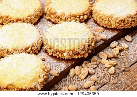 Butter cookies (alfajores) with caramel and peanut on wooden background.