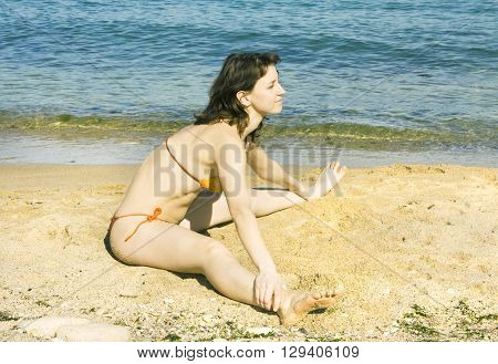 Young European woman with brown hair doing fitness on sea beach.