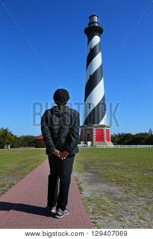 African American woman views the lighthouse in Cape Hatteras National Seashore on North Carolina's Outer Banks on Bodie Island