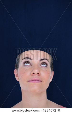 Close-up of beautiful woman looking up against navy blue