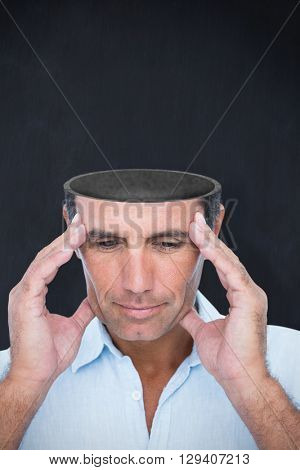 Handsome man thinking with hand on forehead against blackboard