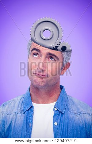 Confused man with grey hair thinking against purple background