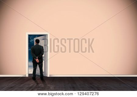 Rear view of classy businessman posing against open door on green wall