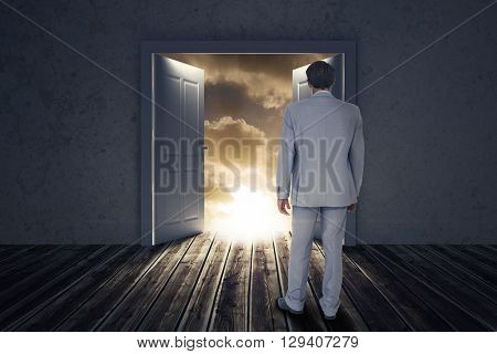 Rear view of businessman walking on white background against open big door on wall