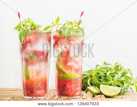 Strawberry mojito summer cocktails with mint and lime in tall glasses. White wall background