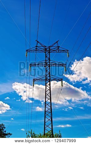 Pylon high-voltage power lines against the blue sky and white clouds
