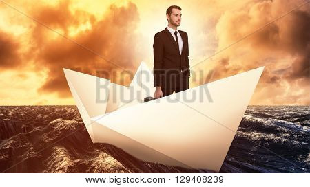 Cheerful businessman holding briefcase while hand in pocket against paper boat floating on the sea